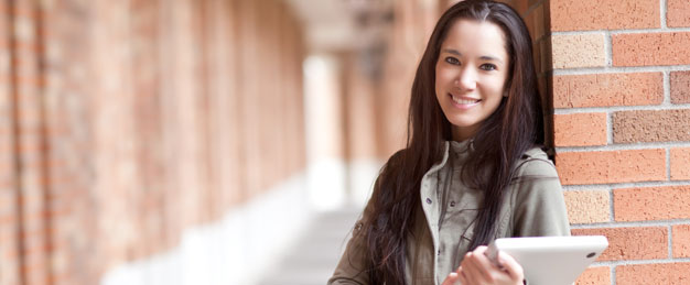 Woman student standing in a brick hallway smiling happily while holding a tablet