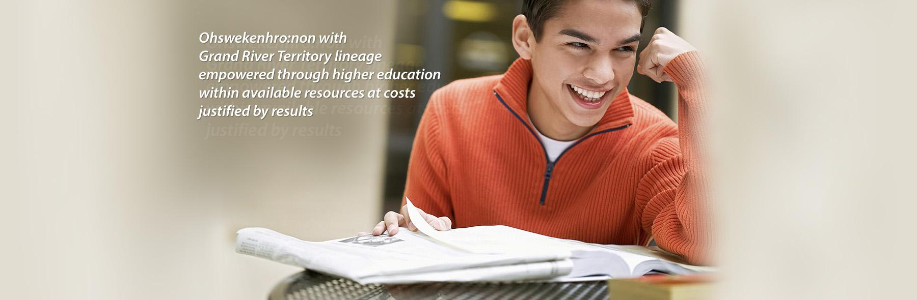 Young man smiling as he studies from a textbook