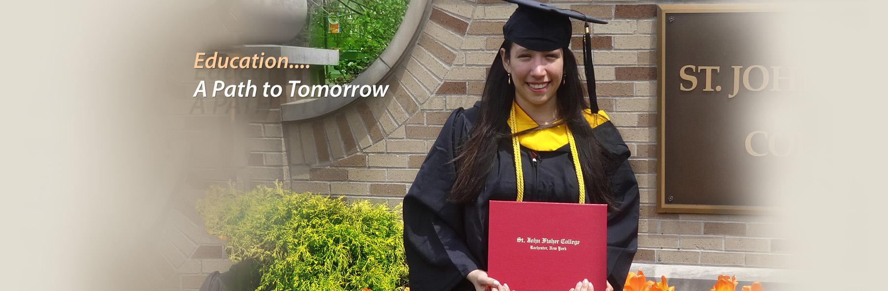 Young woman in graduation gown and mortar board holds her diploma